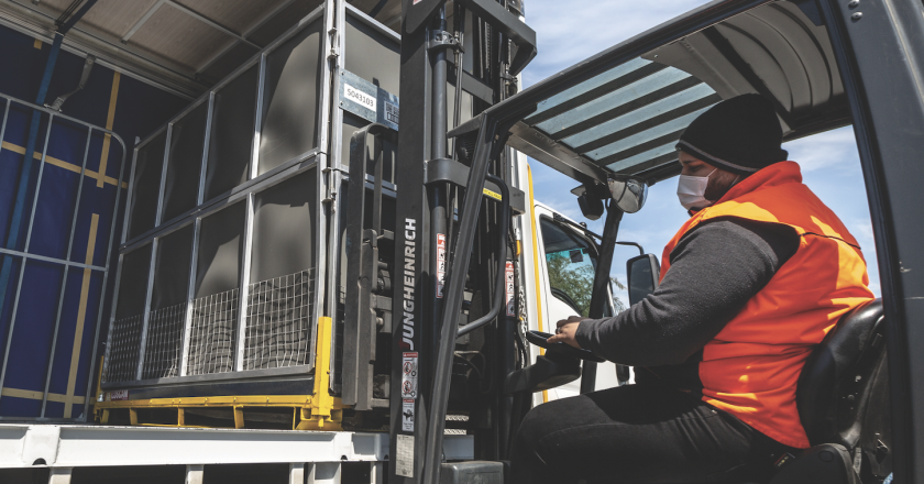 Man loading truck with forklift